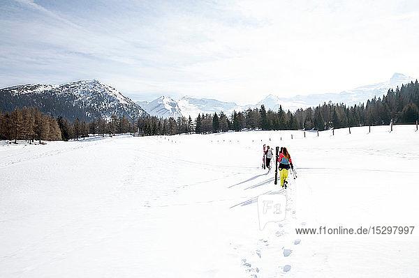 Fünf jugendliche Skifahrerinnen mit Skiern in verschneiter Landschaft  Rückansicht  Tirol  Steiermark  Österreich