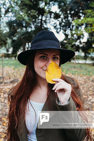 Young woman with long red hair holding autumn leaf on nose in park  portrait