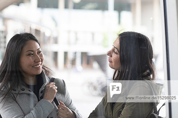 Friends talking in front of shop window