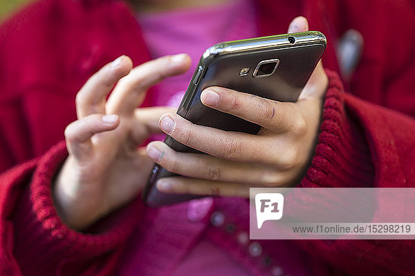 Hands of little girl using smartphone  close-up