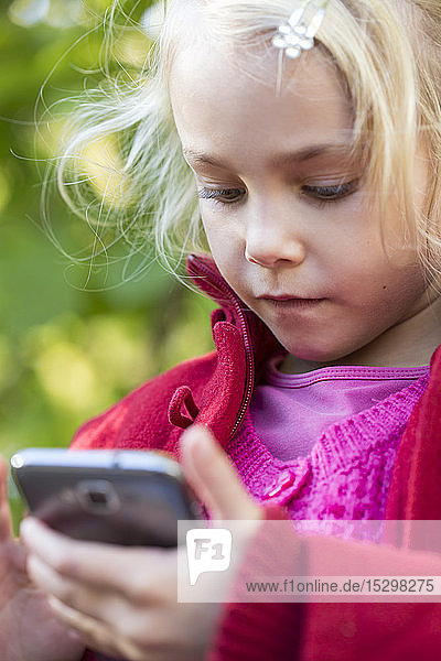 Portrait of little girl using smartphone