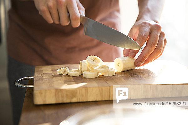 Männerhand beim Bananenschneiden mit dem Küchenmesser