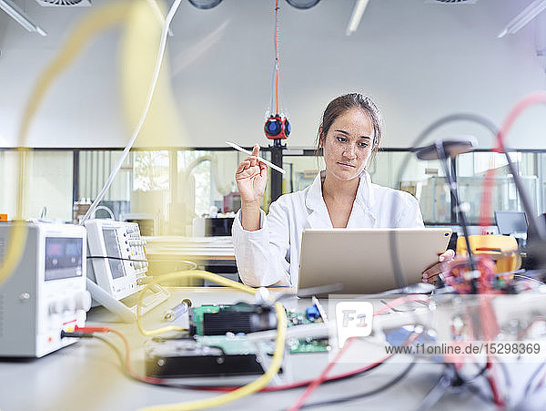 Female technician working in research laboratory  holding pencil in front of tablet