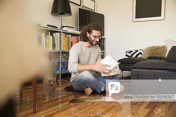 Junger Mann sitzt auf dem Boden im Wohnzimmer und packt ein Geschenk aus