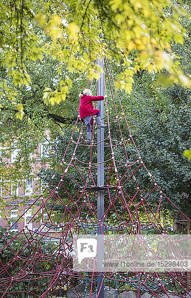 Little girl climbing on jungle gym in autumn