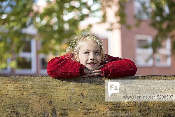 Portrait of blond little girl leaning on wooden railing