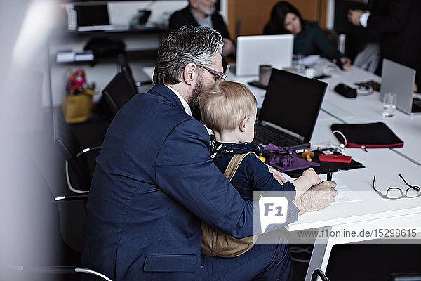 Geschäftsmann mit Sohn arbeitet am Konferenztisch  während die Kollegen im Hintergrund Geschäftsmann mit Sohn arbeitet am Konferenztisch, während die Kollegen im Hintergrund