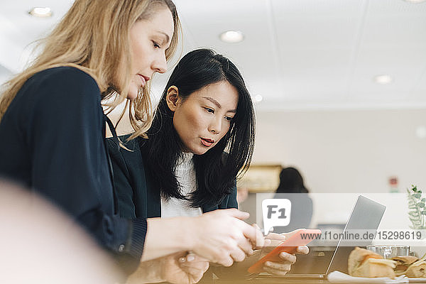 Weibliche Kollegen  die Smartphones benutzen  während sie am Konferenztisch im Sitzungssaal sitzen