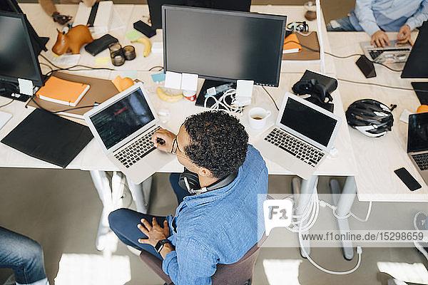 Hochwinkelansicht eines Computerhackers mit Laptop  der im Büro am Schreibtisch sitzt