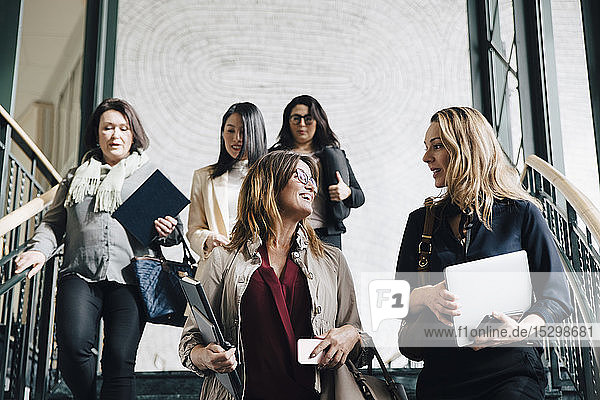 Low angle view of multi-ethnic female entrepreneurs moving down on staircase in office