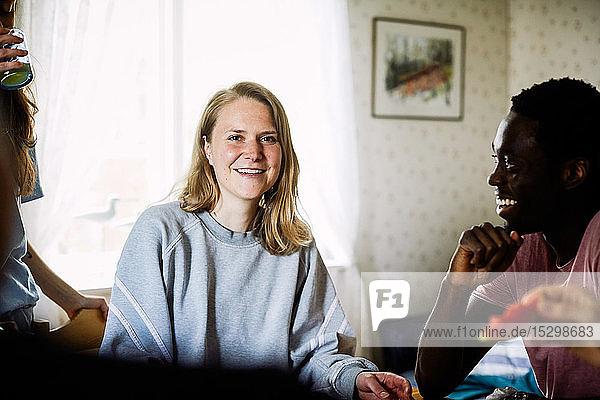Porträt einer lächelnden jungen Frau  die sich zu Hause mit Freunden trifft