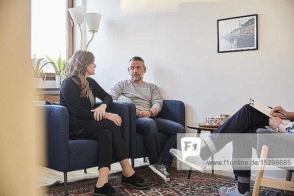 Paar redet  während es mit dem Therapeuten im Gemeindezentrum sitzt