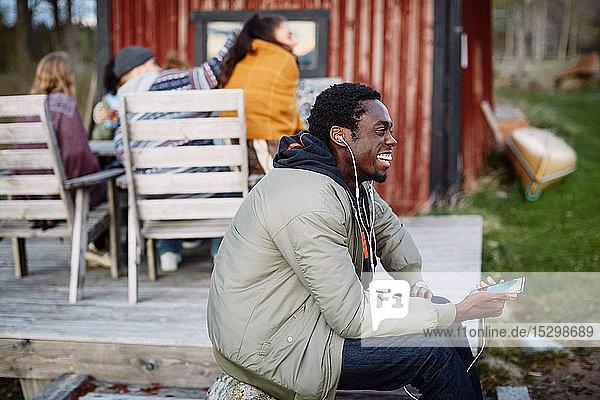 Fröhlicher junger Mann benutzt Smartphone  während sich Freunde bei Sonnenuntergang im Hintergrund unterhalten