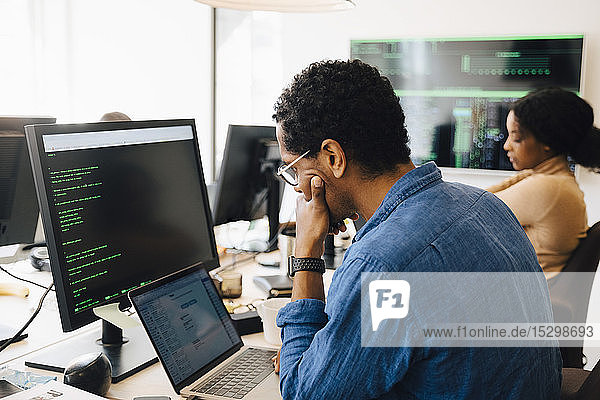 Seitenansicht einer männlichen it professional mit Laptop  während sie neben einer weiblichen Mitarbeiterin im Büro sitzt