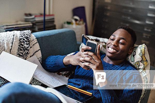 Lächelnder Teenager nutzt soziale Medien  während er bei den Hausaufgaben im Wohnzimmer auf dem Sofa liegt