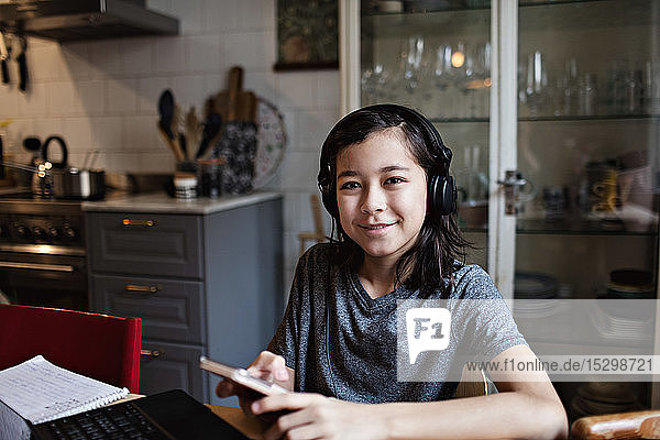 Portrait of smiling boy using mobile phone for E-learning at home
