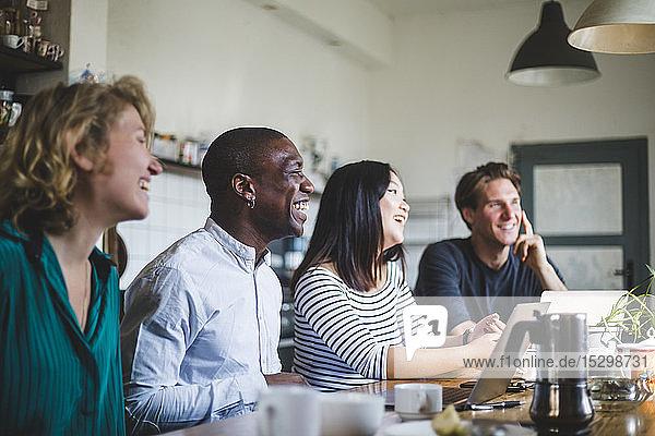 Lächelnde Unternehmer sitzen  während sie im Büro auf den Schreibtisch schauen