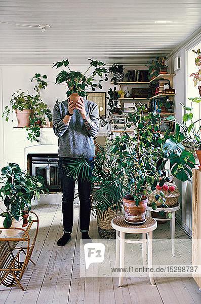 Mann hält Topfpflanze in voller Länge vor dem Gesicht stehend zu Hause
