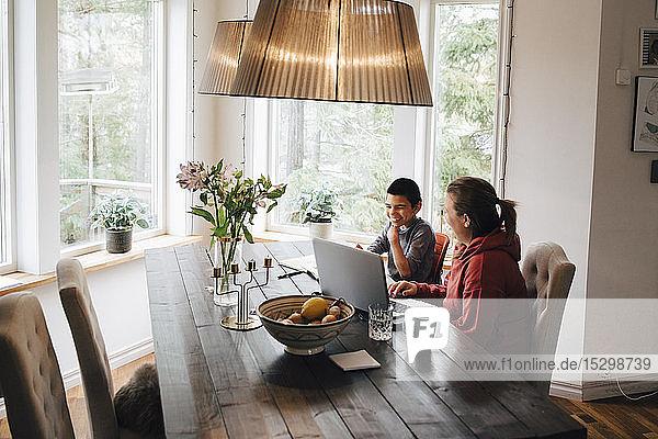 Hochwinkelaufnahme einer Mutter mit autistischem Sohn mit Laptop auf dem Tisch  während sie zu Hause sitzt