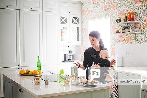 Mutter benutzt Mobiltelefon  während sie ihre Tochter in der Küche zu Hause trägt