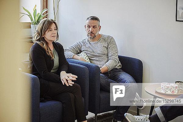 Unzufriedenes Paar teilt Probleme mit dem Therapeuten  während es im Gemeindezentrum sitzt