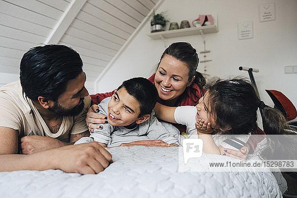 Glückliche Familie  die zu Hause im Bett liegt und sich unterhält