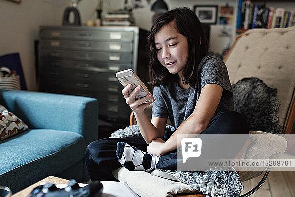 Lächelnder Junge benutzt Mobiltelefon  während er auf einem Stuhl im Wohnzimmer sitzt