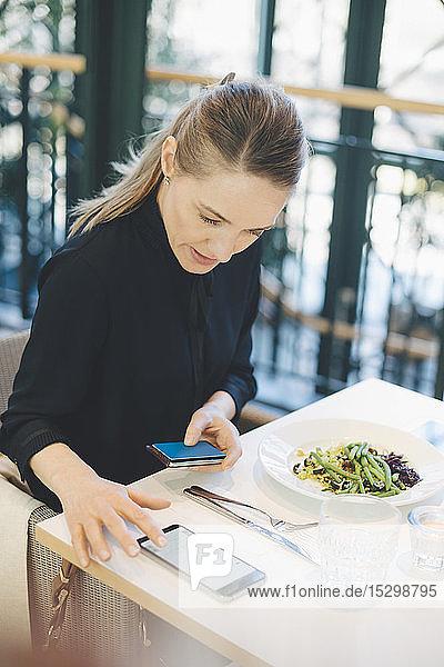 Selbstbewusste Geschäftsfrau benutzt ein Smartphone  während sie mit Kreditkarte in der Cafeteria im Büro sitzt