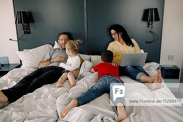 Glückliche Familie im Hotelzimmer im Bett während der Ferien