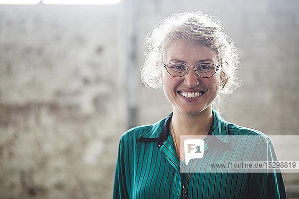 Porträt einer lächelnden blonden Programmiererin  die im Kreativbüro steht Porträt einer lächelnden blonden Programmiererin, die im Kreativbüro steht
