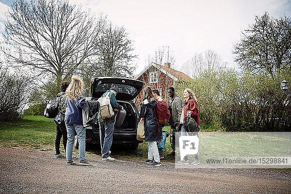 Freundinnen und Freunde  die auf der Straße gegen den Himmel Gepäck aus dem Kofferraum nehmen