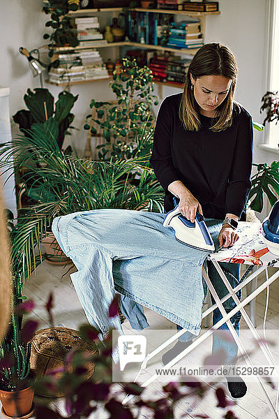 Full length of woman ironing shirt on board in room at home
