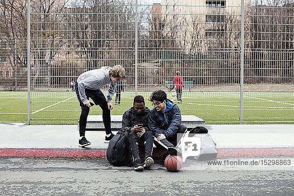 Teenager sieht Freunde an  die soziale Medien auf dem Bürgersteig gegen den Fußballplatz in der Stadt nutzen Teenager sieht Freunde an, die soziale Medien auf dem Bürgersteig gegen den Fußballplatz in der Stadt nutzen