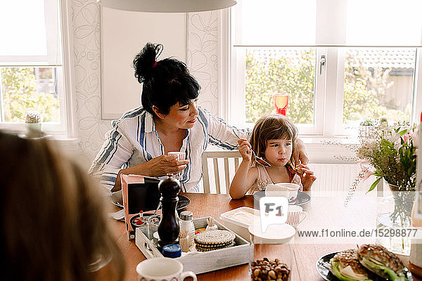 Mother looking at daughter having breakfast on dining table