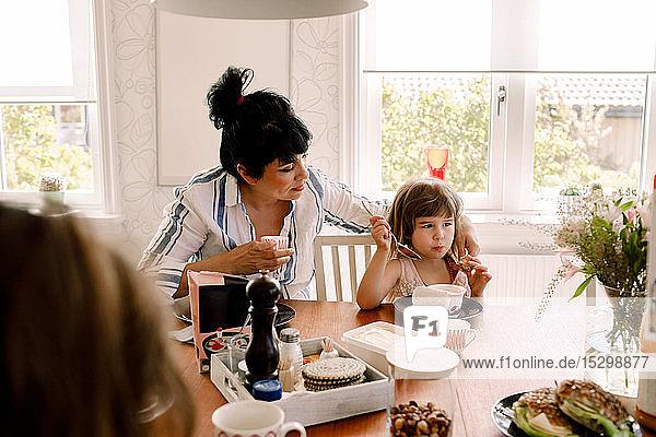 Mutter sieht Tochter beim Frühstück auf dem Esstisch an