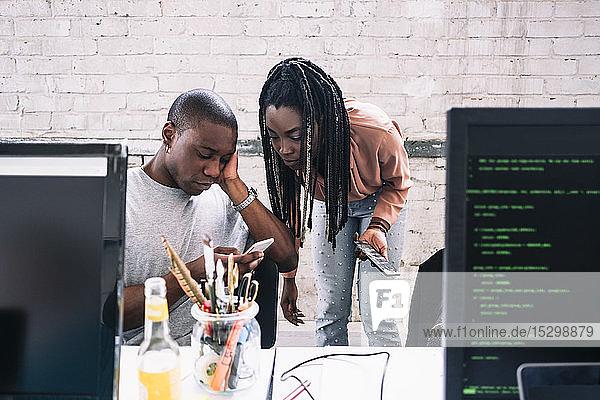 Junge Geschäftsfrau betrachtet einen Geschäftsmann  der ein Smartphone im Kreativbüro benutzt Junge Geschäftsfrau betrachtet einen Geschäftsmann, der ein Smartphone im Kreativbüro benutzt