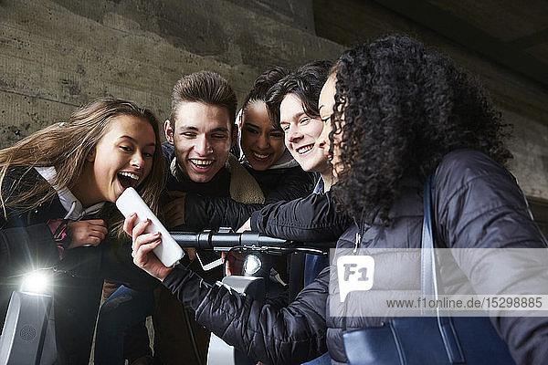 Teenager-Mädchen zeigt glücklichen männlichen und weiblichen Freunden ihr Handy
