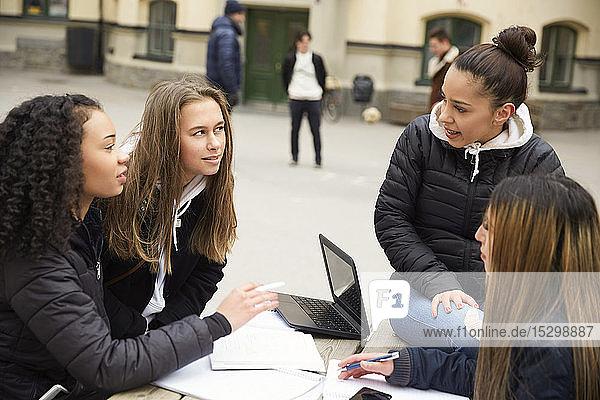 Multi-ethnische Freundinnen diskutieren bei Tisch auf dem Schulhof Multi-ethnische Freundinnen diskutieren bei Tisch auf dem Schulhof