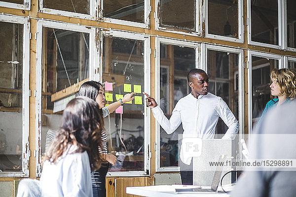Seriöse Kreative  die auf Haftnotizen zeigen  während sie mit dem Team im Büro diskutieren