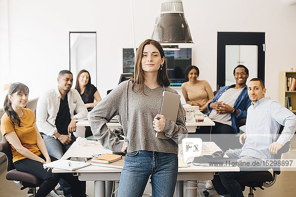 Portrait of confident businesswoman holding laptop while colleagues sitting at desk in office