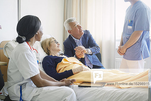 Couple looking at medical professionals in hospital ward