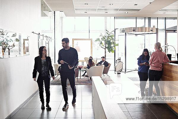 Eine reife Geschäftsfrau diskutiert mit einem männlichen Kollegen  während sie in der Lobby mit Kollegen im Hintergrund arbeitet