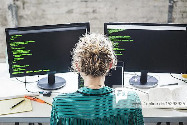 Schrägansicht einer IT-Expertin bei der Arbeit an Computerprogrammen am Schreibtisch im Kreativbüro Schrägansicht einer IT-Expertin bei der Arbeit an Computerprogrammen am Schreibtisch im Kreativbüro