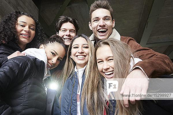 Niedrigwinkel-Porträt von fröhlichen männlichen und weiblichen Teenager-Freunden unter der Brücke Niedrigwinkel-Porträt von fröhlichen männlichen und weiblichen Teenager-Freunden unter der Brücke