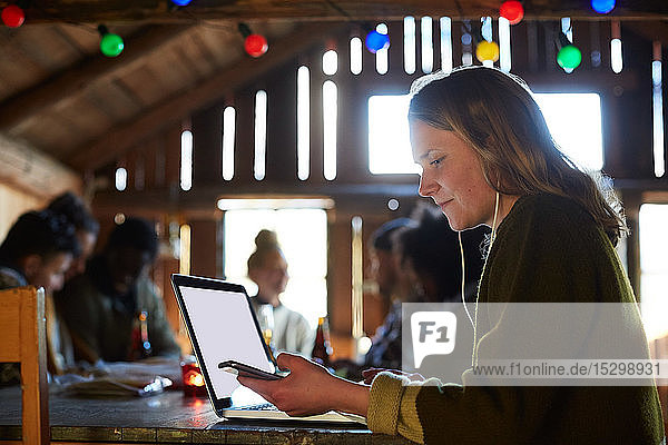 Young woman using laptop on table while friends talking in background at home