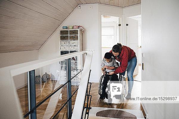 Mutter befestigt Rollstuhl-Schnalle für behinderten Sohn zu Hause