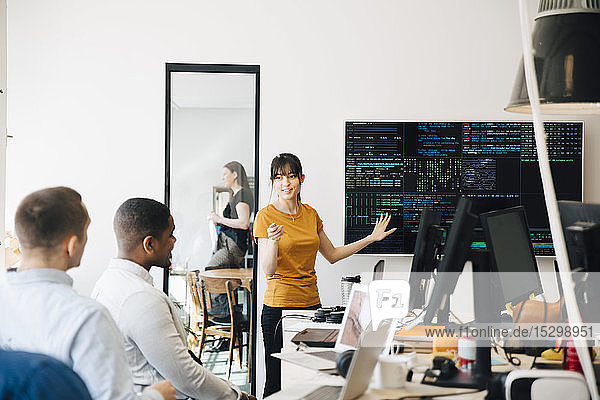 Weiblicher Hacker interagiert mit Kollegen während einer Präsentation im Büro