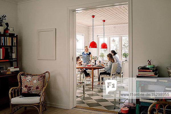 Mütter und Töchter beim Frühstück am Esstisch durch die Tür gesehen