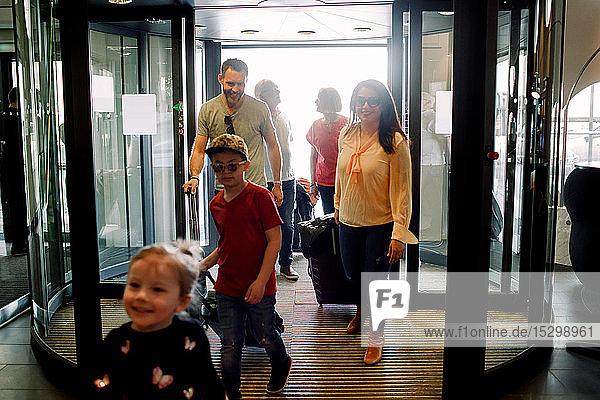 Lächelnde Familie betritt Hotel während des Urlaubs