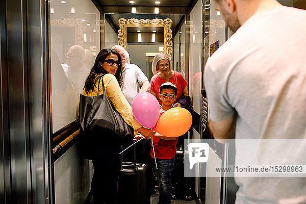 Familie schaut den Mann an  während sie im Aufzug steht